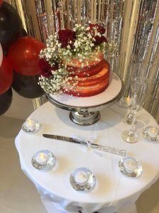 rimma's wedding cakes 2 tier wedding cake with red buttercream on stand at reception