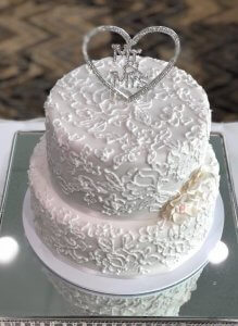 2 tier wedding cake on stand at reception
