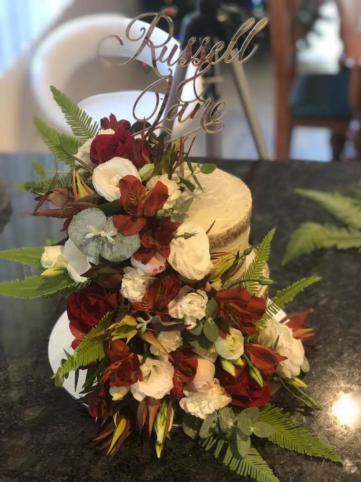 two tier buttercream rustic style wedding cake with fresh flowers