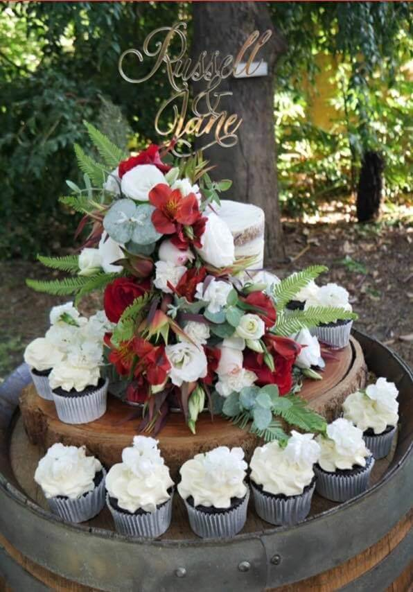 naked wedding cake with fresh flowers and cupcakes