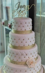 four tier white pearl studded wedding cake