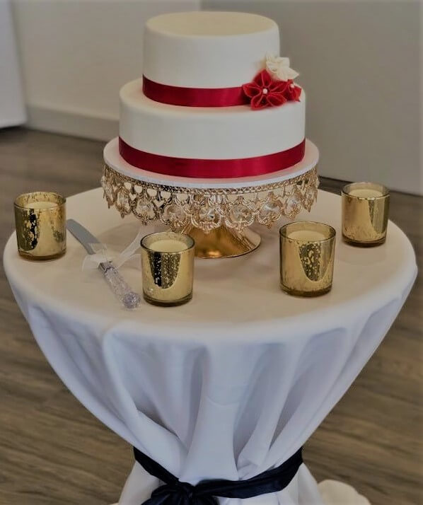 two tier red and white wedding cake on stand