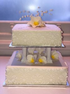 two tier white fondant wedding cake on pillars