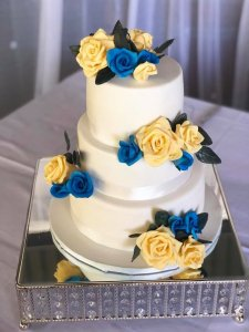 three tier white wedding cake with blue and yellow hand made sugar flowers