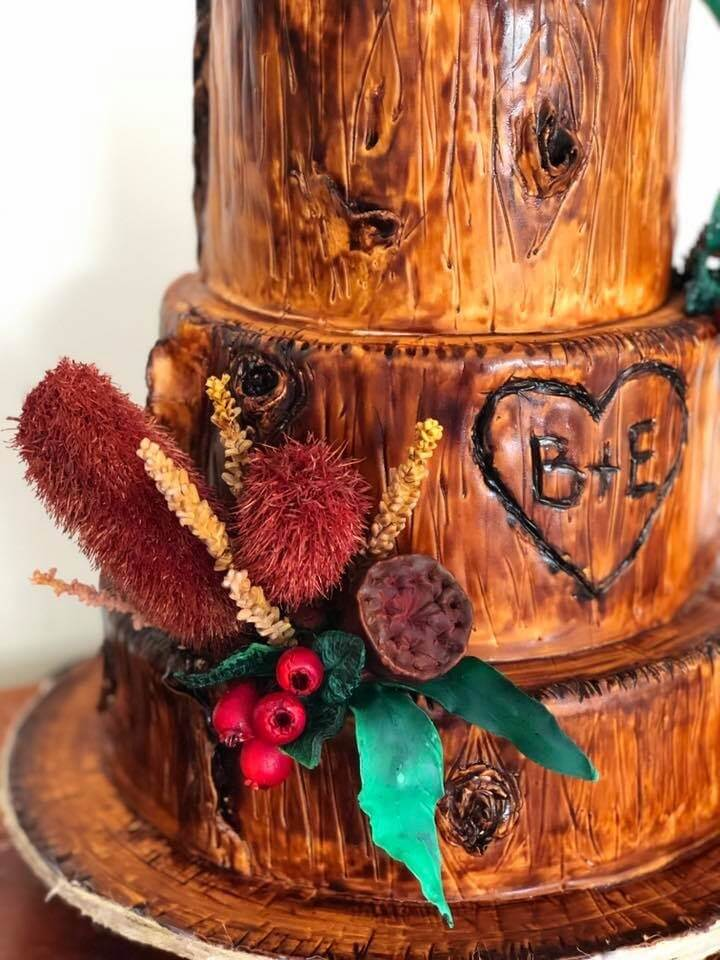 timber themed wedding cake with couples initials carved into timber