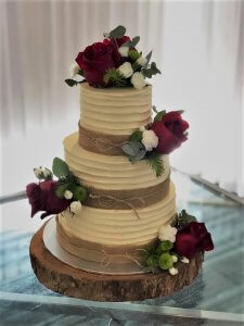 buttercream wedding cake with beautiful full red roses and hession ribbon
