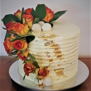 buttercream birthday cake with fresh flowers and gold leaf