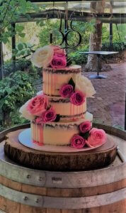 pink buttercream wedding cake on solid timber cake board