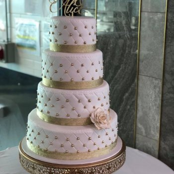 4 tier wedding cake with gold pearls and quilted fondant finish