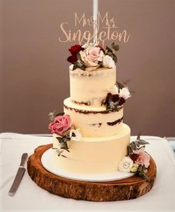 3 tier buttercream wedding cake on solid timber cake stand