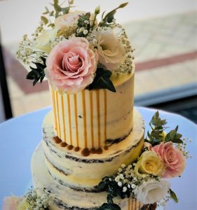 3 tier semi naked wedding cake with caramel dripping with white and pink fresh flowers by rimma's wedding cakes perth
