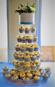 white cupcake tower with blue ribbon and fresh flowers by rimma's wedding cakes perth