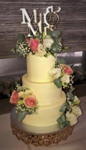 3 tier wedding cake with fresh flowers and golden cake topper